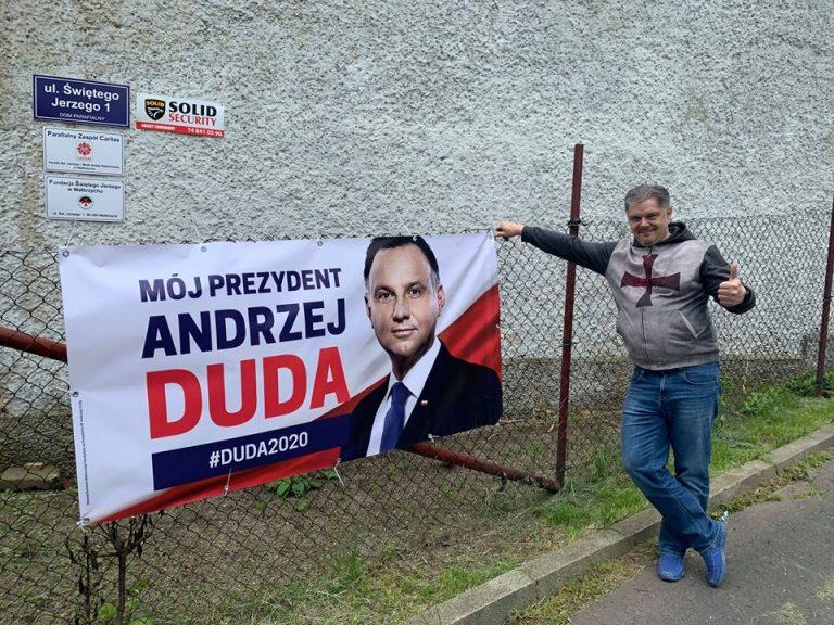 """Ksiądz wiesza baner wyborczy Andrzeja Dudy na płocie przy budynku Caritas. """"Po pracy"""" już może?"""